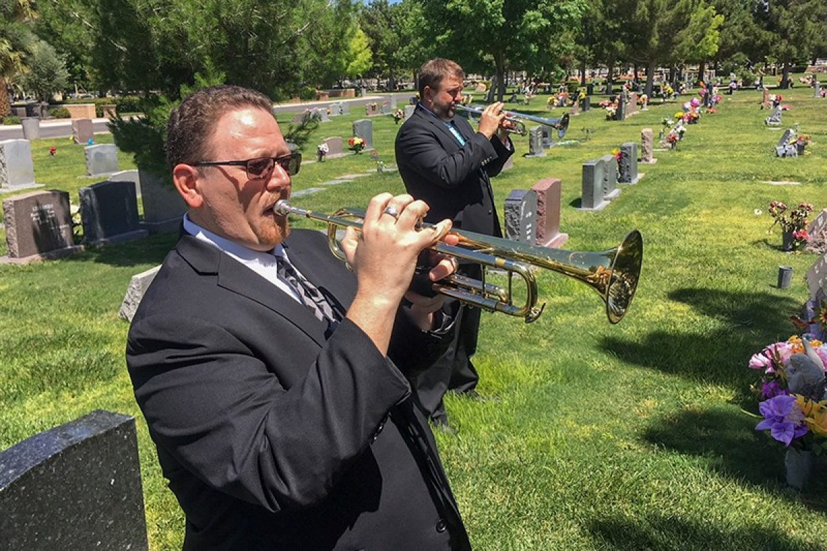 Men in suits at funeral playing trumpets