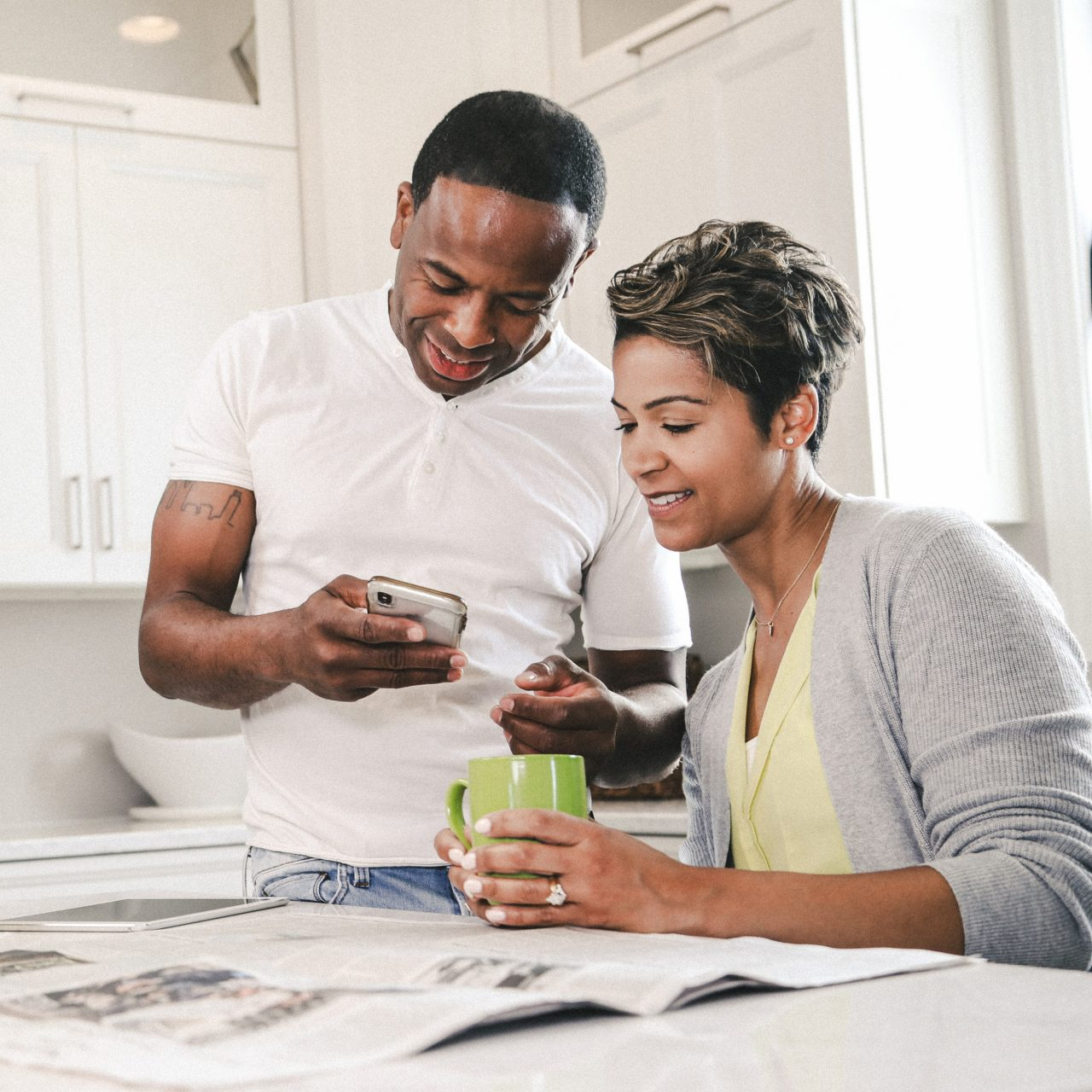 Couple looking at devices and news paper in kitchen drinking coffee