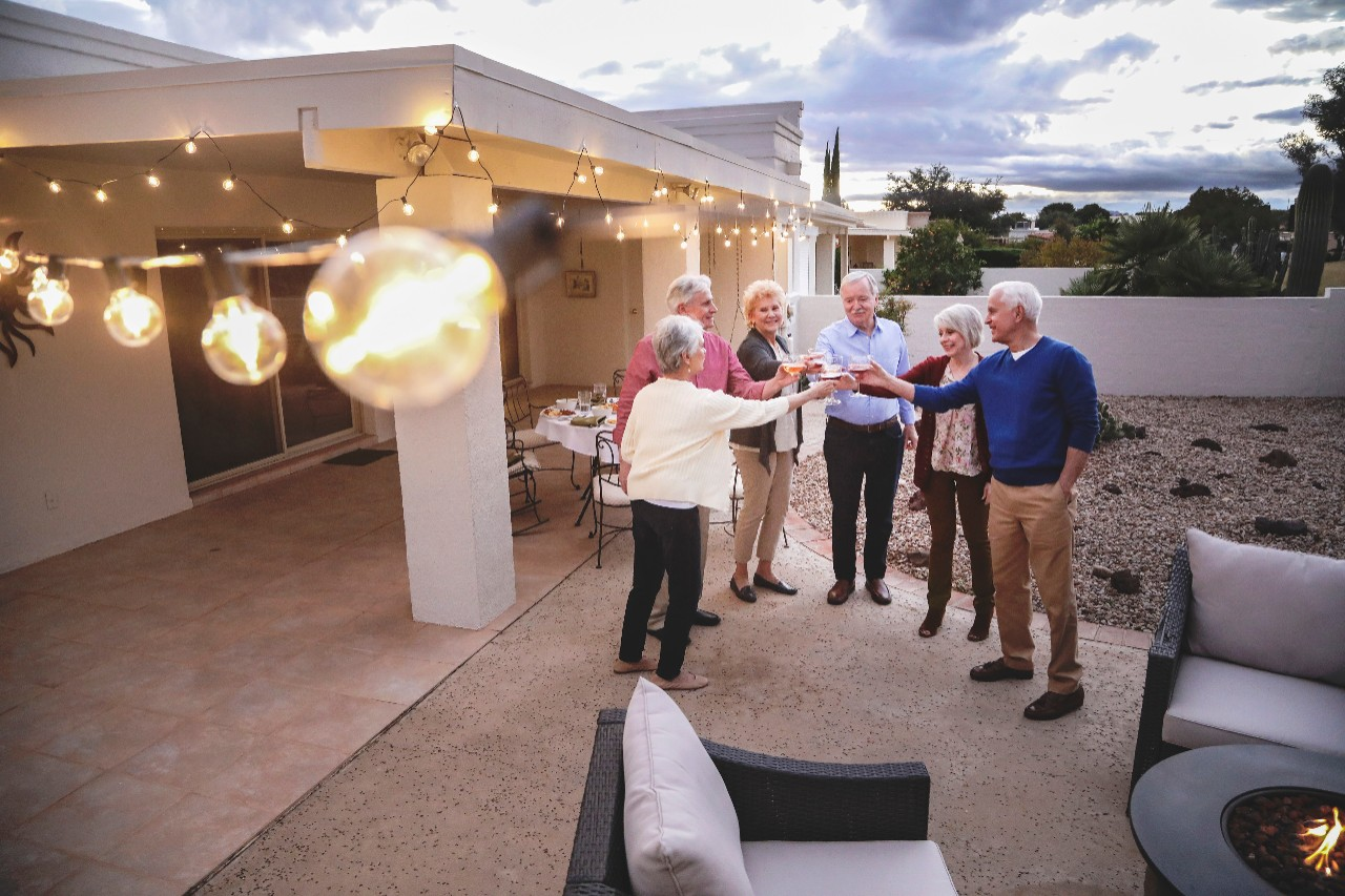 Seniors cheers in celebration on back patio of house
