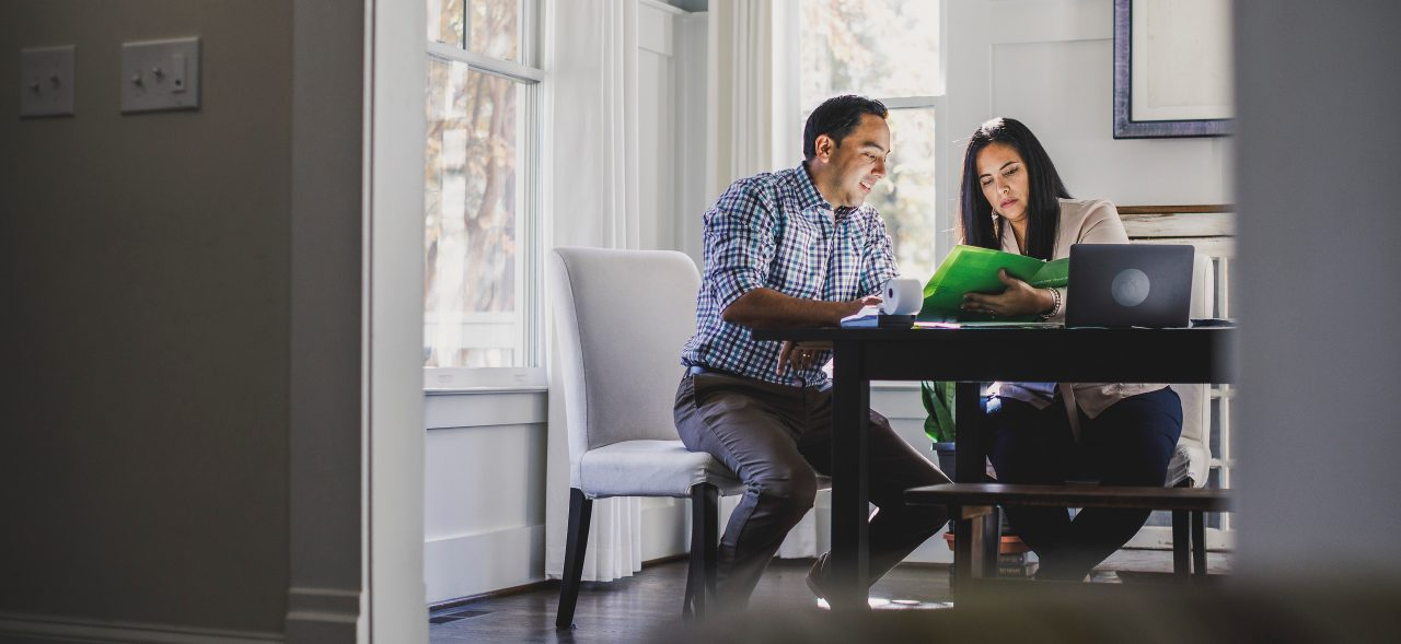 Couple sitting at dining table reviewing expenses with paper and computer