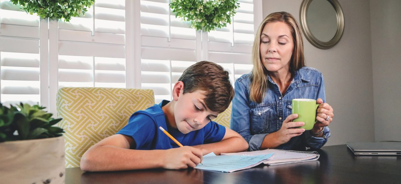 Mother helping son with homework sitting at kitchen table