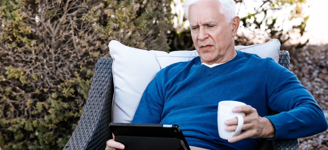 Senior man sitting on patio furniture drinking coffee and looking at tablet