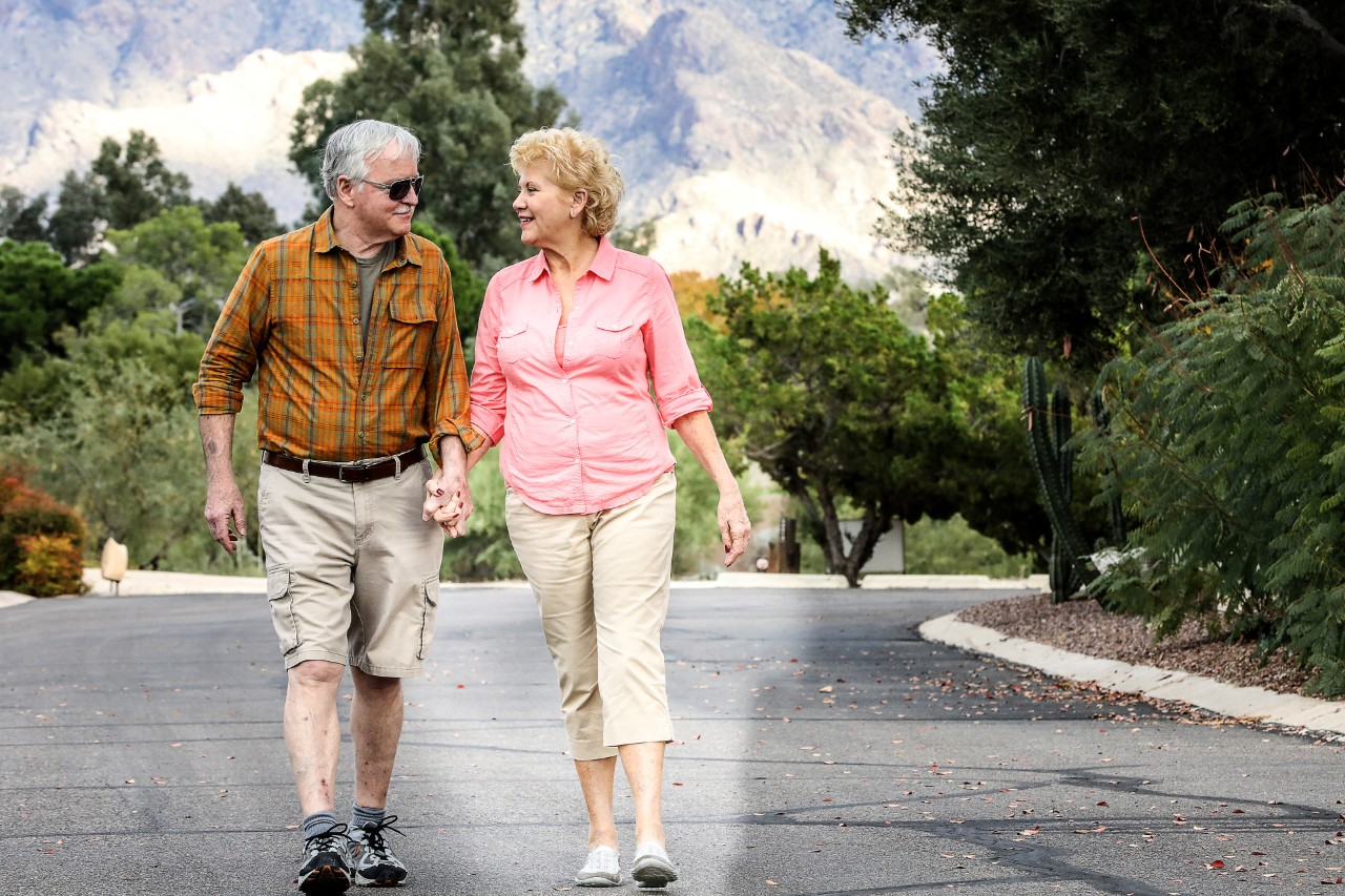 Senior couple holding hands walking on the road
