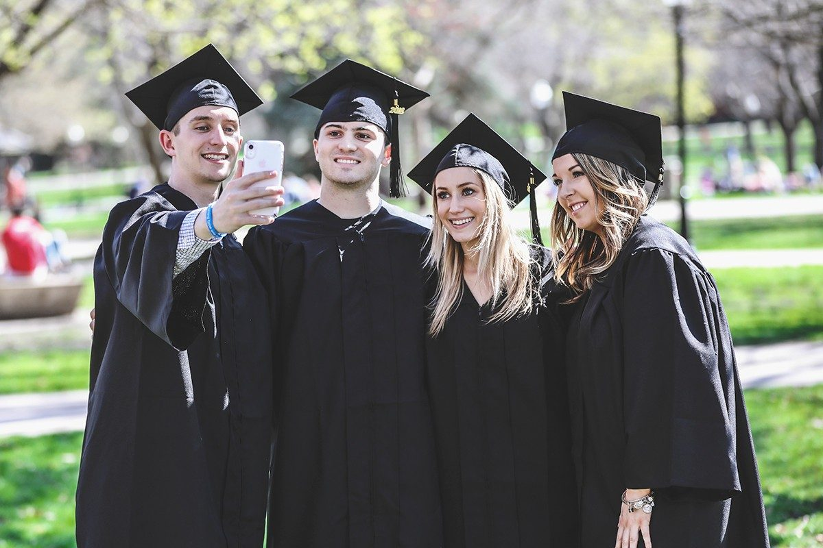Four graduates in cap and gown taking selfie picture in park