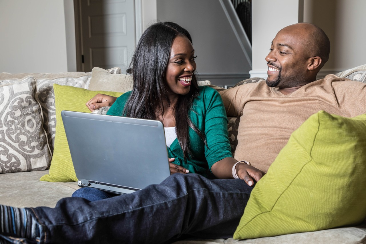 African American couple sitting on couch with laptop