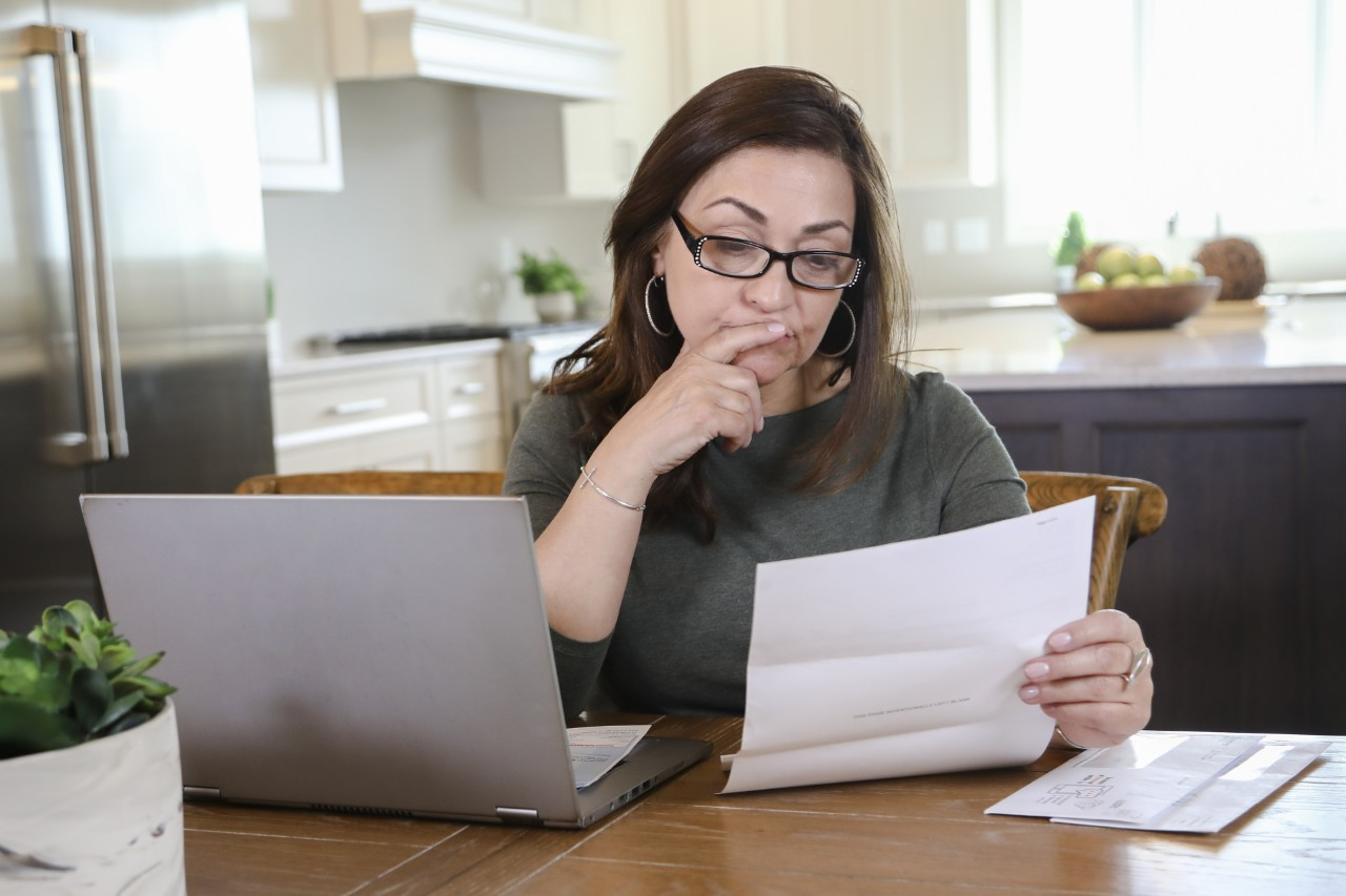 Woman using laptop and reviewing bill