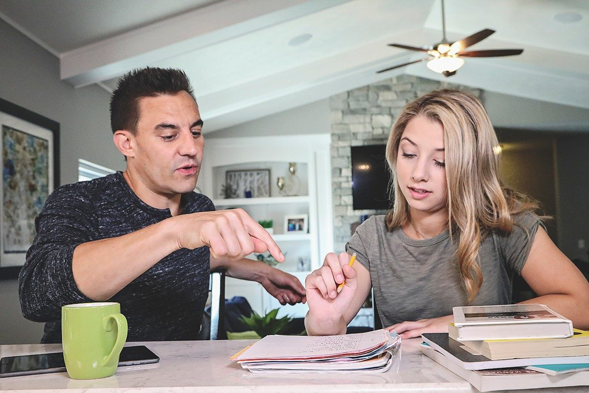 Father helping daughter with homework at kitchen table