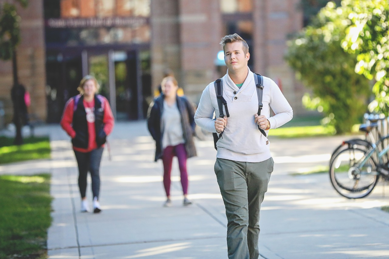 Male college student with backpack walking on campus